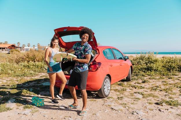 De jonge zwarte surfplank van de mensenholding dichtbij auto door kust