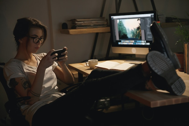 De jongedameontwerper binnenshuis bij nacht speelt telefonisch spelen