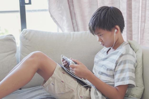 De jongelui preteen aziatische console van het jongens speelspel, het sociale distantiëren, isolatie, het concept van het verslaafdeeffect