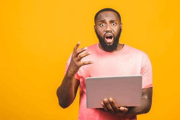 De jongelui verraste afrikaanse mens die en laptop computer bevinden zich met behulp van over gele achtergrond wordt geïsoleerd.