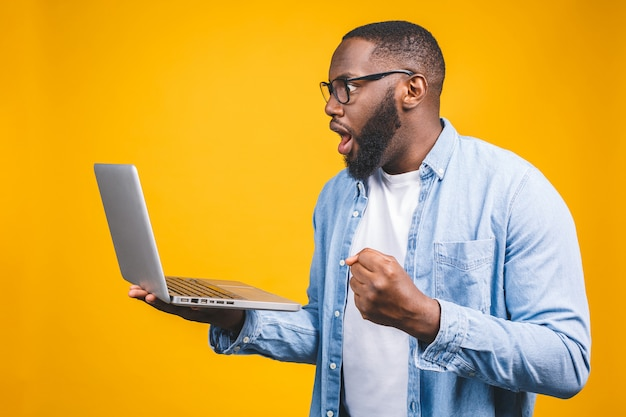 De jongelui verraste afrikaanse mens die en laptop computer bevinden zich met behulp van