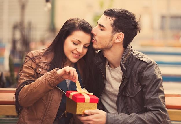 De jongeman geeft een jong meisje in het café een cadeau en ze kussen elkaar.