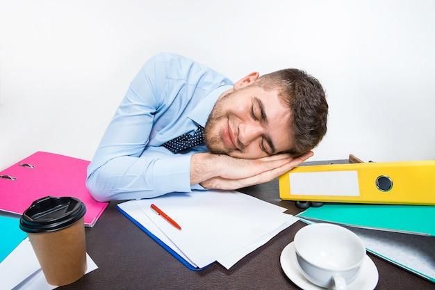 De jongeman slaapt tijdens zijn werkuren brutaal op het bureaublad