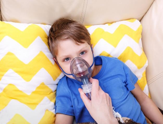De jongen ademt door verstuiver. zieke chid met pediatrische vernevelaar.