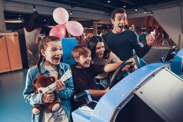 De jongen berijdt auto in arcade. familie is aan het juichen en helpen.