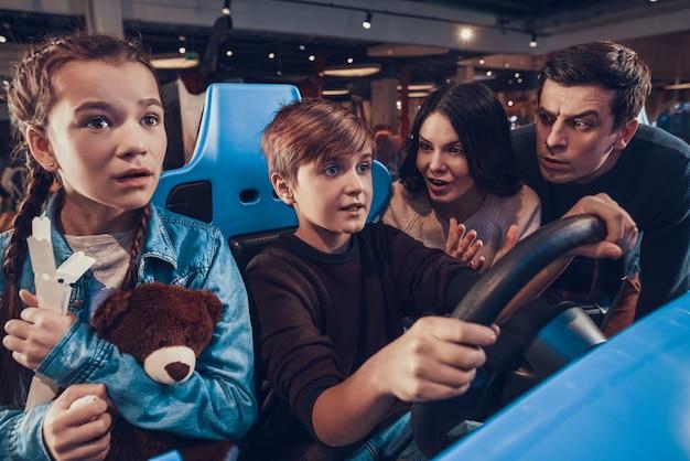 De jongen berijdt auto in arcade. familie juicht toe.
