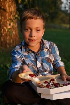 De jongen biedt een stuk pizza aan.