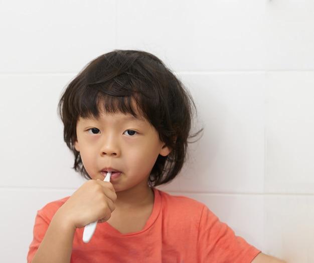 De jongen borstelt zijn tanden in badkamers