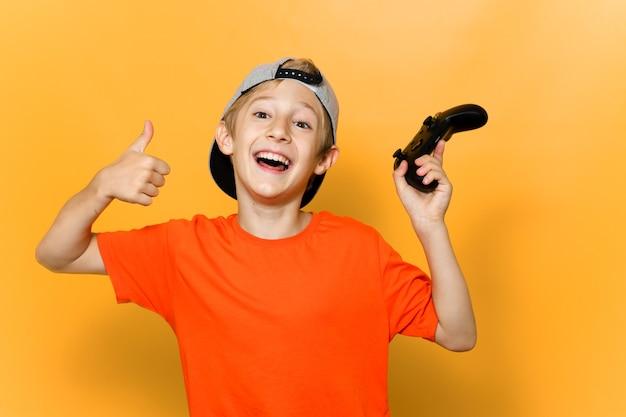 De jongen computer gamers verheugt zich over de overwinning met een joystick in zijn hand en hief ze op