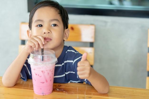 De jongen die een roze melk drinkt