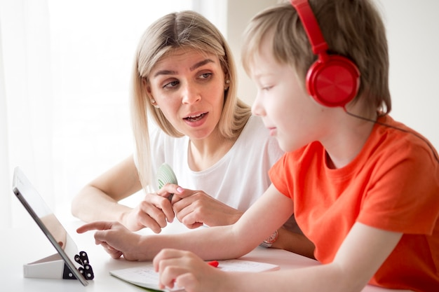 De jongen die hoofdtelefoons draagt en schrijft naast zijn moeder
