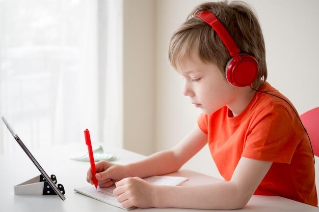 De jongen die hoofdtelefoons draagt en schrijft