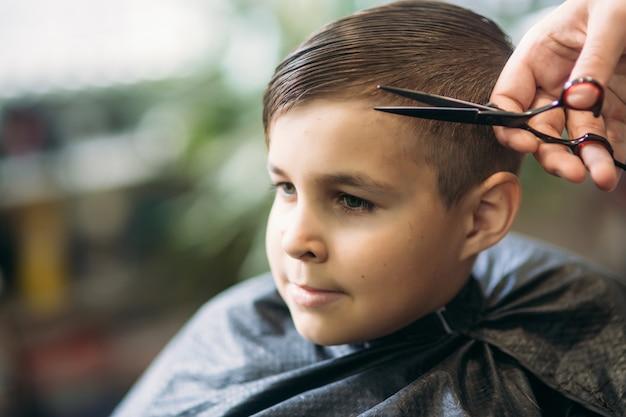 De jongen die in de kapperszaak door een schaar wordt geknipt