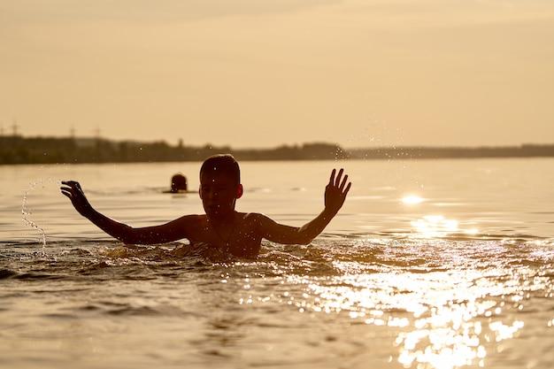 De jongen die in rivier bij zonsondergang speelt. handen omhoog bij het hoofd. plezier en jeugd concept.