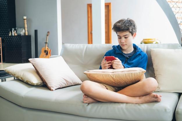 De jongen die thuis online spel op smartphone speelt.