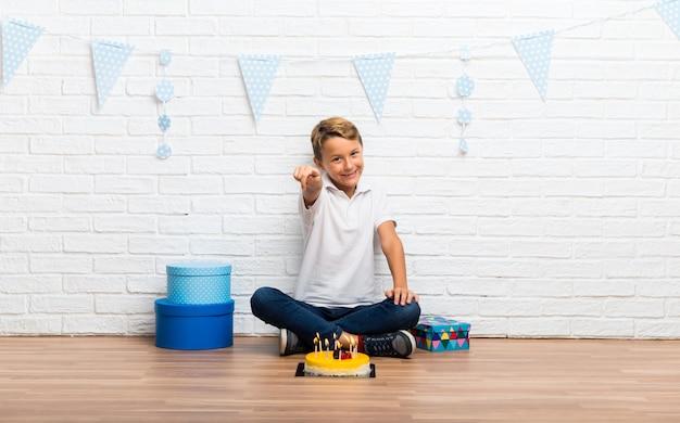 De jongen die zijn verjaardag met een cake viert richt vinger op u