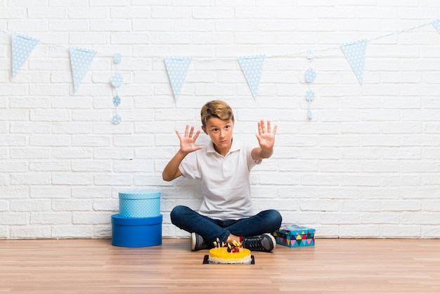 De jongen die zijn verjaardag viert met een cake is een beetje nerveus en bang