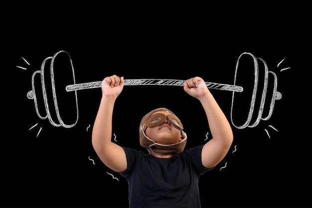 De jongen doet zich voor als een superheld en oefent door gewichten op te heffen.