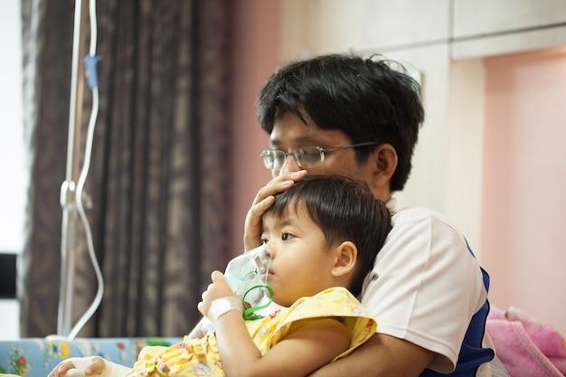 De jongen draagt een zuurstofmasker in de ziekenhuisafdeling, de schoot van de jongvader