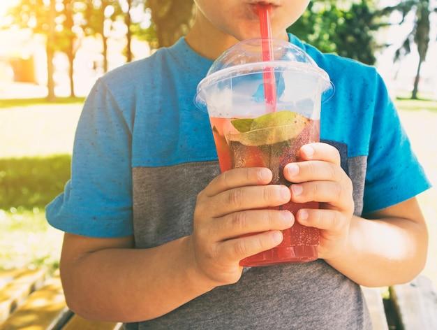 De jongen drinkt de roze limonade uit de plastic beker