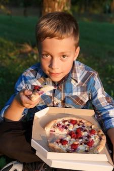 De jongen eet een stuk pizza.