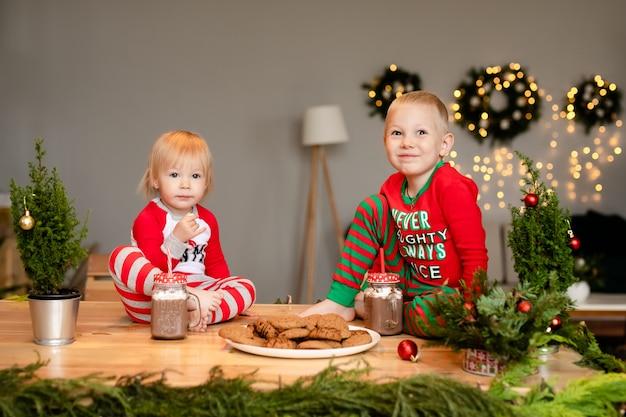 De jongen en het meisje drinken de hete chocolademelk van kerstmis