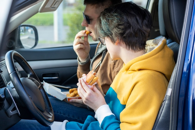 De jongen en het meisje eten fastfood in de auto zitten en praten over ongezond voedsel