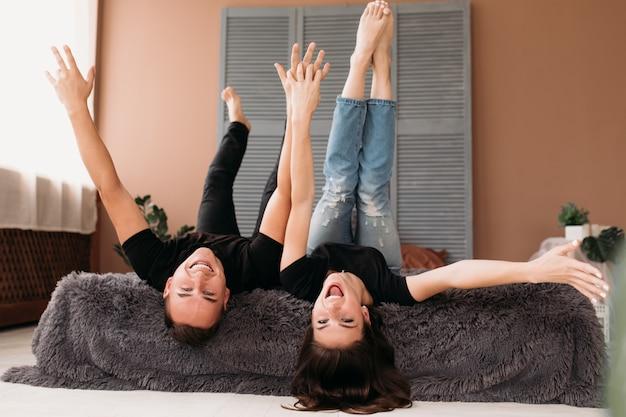 De jongen en het meisje heffen hun benen op liggend op een bed in een comfortabele ruimte op