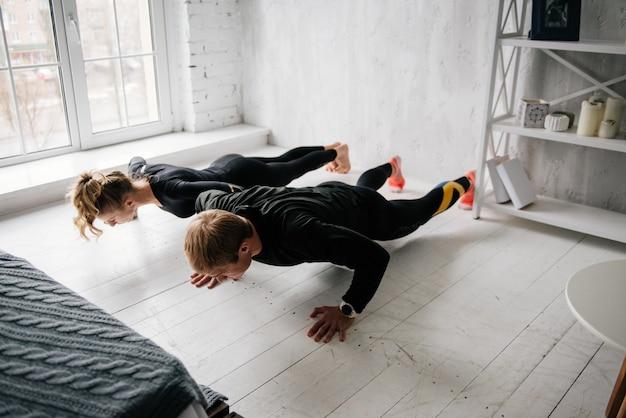 De jongen en het meisje in trainingspak. zwart sportuniform. mannelijke en vrouwelijke atleten. opgepompt lichaam. opdrukken. ochtendtraining. set oefeningen voor lichaam. klassen in paren. samen thuis trainen.