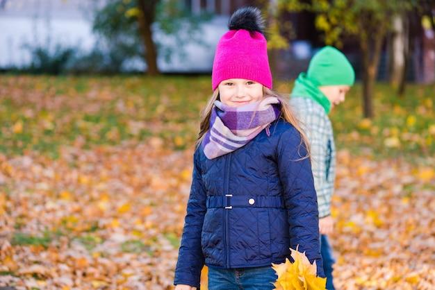 De jongen en het meisje verzamelen buiten geel esdoorngebladerte. het glimlachende meisje onderzoekt camera.