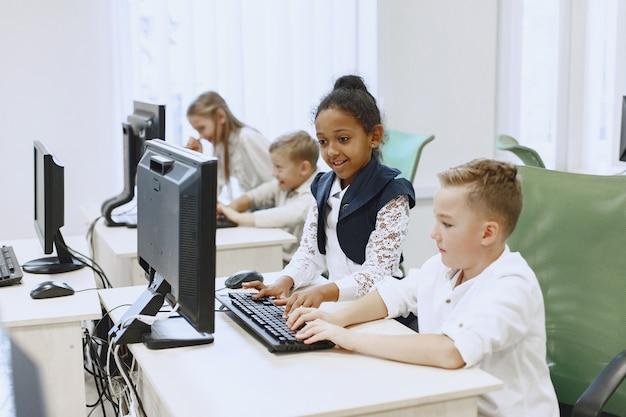 De jongen en het meisje zitten aan tafel. afrikaans meisje in de klas van de informatica. kinderen spelen van computerspelletjes.