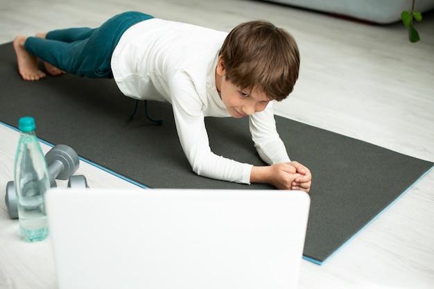 De jongen gaat thuis online sporten. het kind doet oefeningen in de kamer.