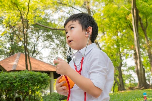 De jongen gebruikt stethoscopen en speelt met het oranje fruitsymbool