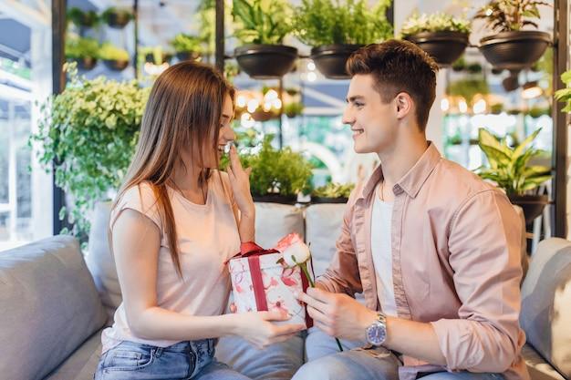 De jongen geeft het mooie meisje een roos en een verrassing