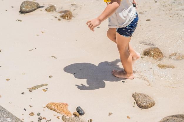 De jongen geniet van de tropische zee en het strand.