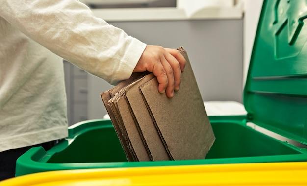 De jongen gooit het karton in een van de drie vuilnisbakken