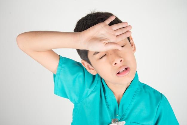 De jongen heeft hoofdpijn van koude of griep op hogere temperatuur