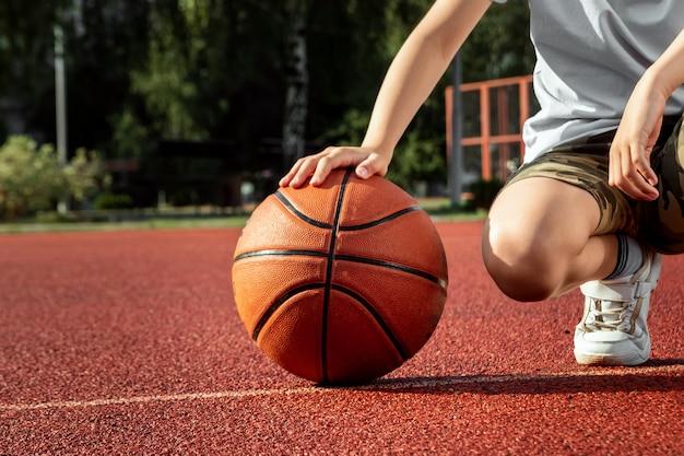 De jongen houdt een basketbalclose-up in zijn handen