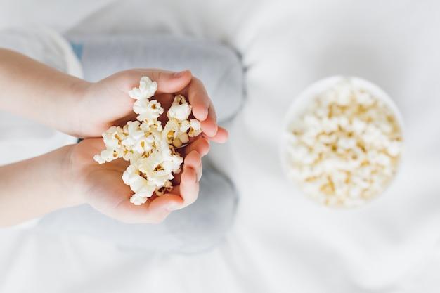 De jongen houdt een handvol popcornclose-up