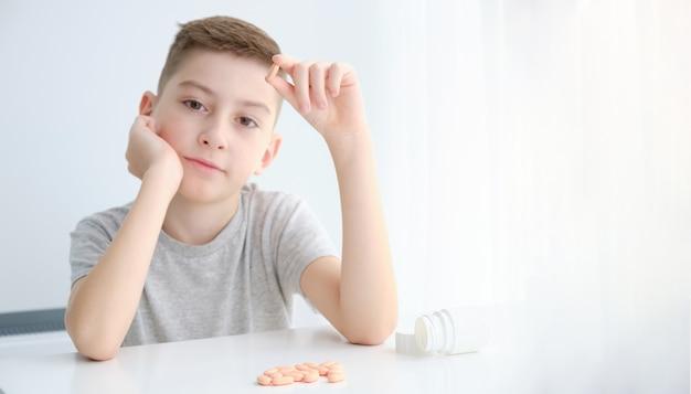 De jongen houdt een pillencapsule in zijn handen. een kind thuis behandelen. gezondheidszorg en medische concept achtergrond.