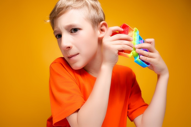 De jongen houdt een siliconen antistress speeltje voor zich, probeert ballen te laten knappen en luistert