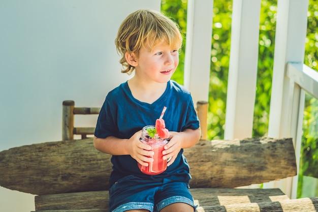 De jongen houdt gezonde watermeloen smoothie in mason-pot met munt en gestreepte rietjes op een hout.