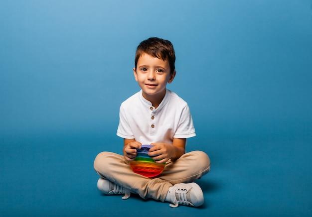 De jongen houdt klappend speelgoed in zijn handen. druk spel. gelukkige jongen met pop-it.