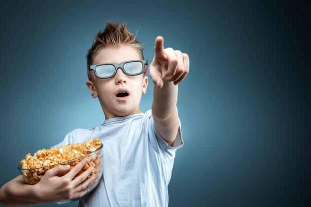 De jongen houdt popcorn in zijn handen en kijkt naar een film in 3d-bril op een blauwe muur. het concept van een bioscoop, films, emoties, verrassing, vrije tijd.