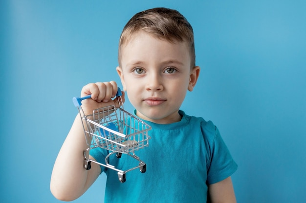De jongen in blauw t-shirt houdt boodschappenwagentje en muntstuk op blauwe achtergrond. winkelen en verkoop concept.
