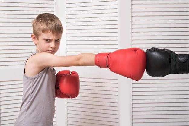 De jongen in bokshandschoenen vecht met man dient een handschoen in.