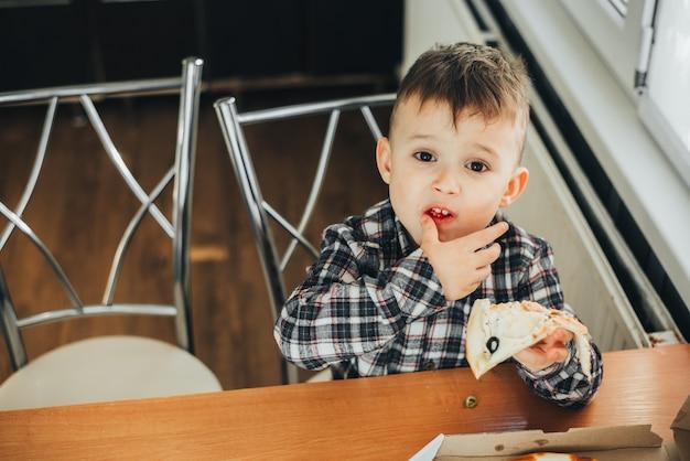 De jongen in de keuken die thuis pizza met zalm eet