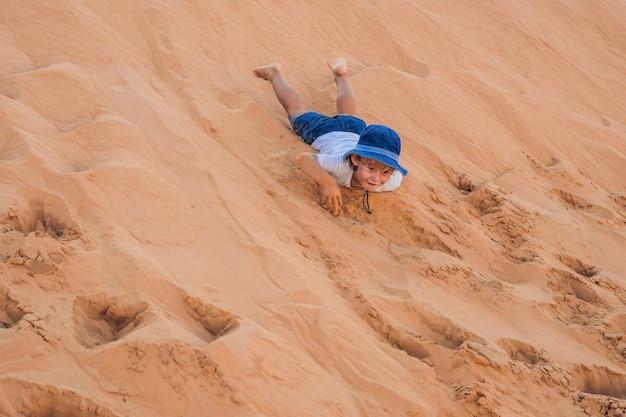 De jongen in de rode woestijn bij zonsopgang die met kinderen reist
