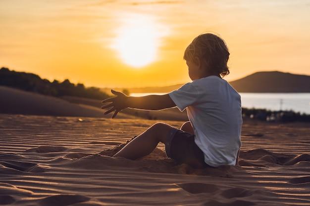 De jongen in de rode woestijn bij zonsopgang. reizen met kinderen concept.