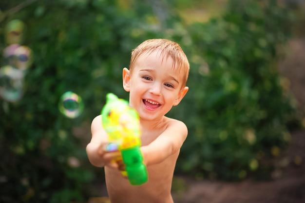 De jongen in de zomer schiet een waterpistool.